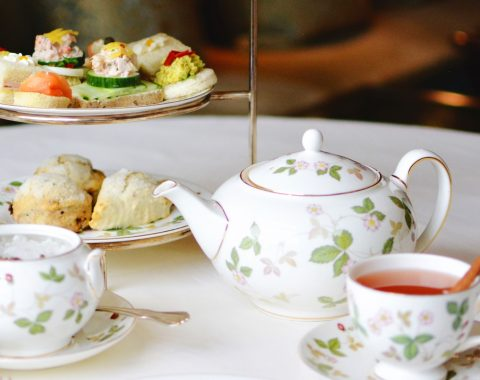 table setup for traditional English afternoon tea service including teapot, scones, tea sandwiches and teacup