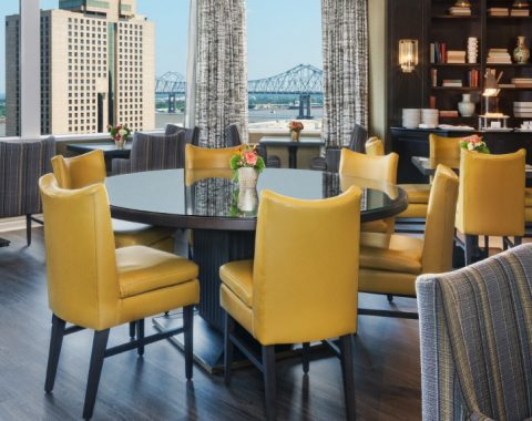 Club Level at Windsor Court hotel features yellow leather chairs, dark wood finishes and sweeping skyline views of New Orleans