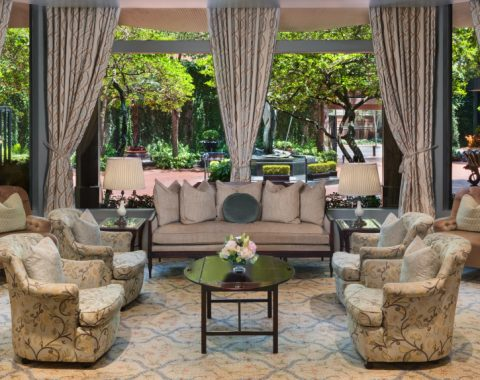The seating area in the lobby of Windsor Court hotel looks out to a lush, green courtyard