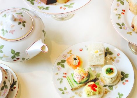 Tea tablescape featuring sandwiches, scones and tea